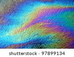 Gasoline that had leaked onto a wet parking lot creates a rainbow oil slick - stock photo