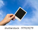 Hand holds a instant photo frame against blue sky - stock photo