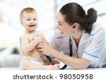 a doctor holding a baby on the hands - stock photo