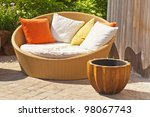 A modern wicker garden sofa or love seat in the home garden. - stock photo