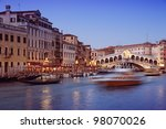 Rialto Bridge and motion blured water bus at Grand Canal in Venice. - stock photo