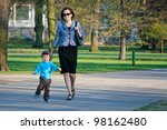 Mother and her two years old son walking in city - stock photo