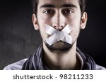 Man with tape over his mouth. - stock photo