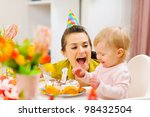Mother and baby having fun at birthday party - stock photo