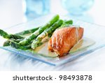 Salmon fillet with asparagus and yellow sauce in horizontal orientation - stock photo