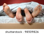 feet of a couple under the blanket - stock photo