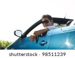 Side view of a man driving his convertible car - stock photo