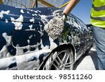Close-up of a man cleaning his car using a sponge - stock photo
