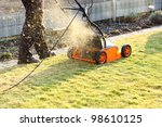 Using a scarifier to improving quality of the lawn - stock photo