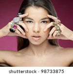 Attractive young woman with diamonds on the hands looking to the camera on the red background - stock photo