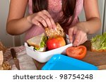 Hands of a woman preparing a lunchbox on the kitchen table - stock photo