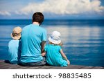 Back view of father and kids sitting on wooden dock looking to ocean - stock photo
