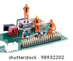 tiny figures of construction engineers examining  integrated circuit - stock photo