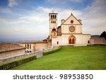 The beautiful Basilica of St. Francis of Assisi located in the town of Assisi, Italy. Photo contains a Tuscan hillside view in the background and a bright blue sky with pretty cloud formations. - stock photo