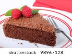 Slice of chocolate cake with raspberries and mint on a plate - stock photo