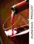 Red wine being poured into wine glass - stock photo