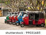 BENDOTTA, SRI LANKA - DECEMBER 04: Row of red, blue and green empty tuk-tuks waits for passengers on December  4, 2011 in Bendotta, Sri Lanka. Tuk-tuk is a popular asian transport as taxi. - stock photo