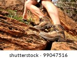 Close up of hiking boots and legs climbing up rocky trail - stock photo