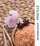 Sea salt bath in wooden bowl with stones and flowers - stock photo