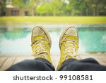 Pair of old shoes on edge of a pool - stock photo