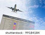 Airplane flying over an information board against blue cloudy sky - stock photo