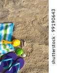 Beach background with flip flop, towel and plastic spade - stock photo