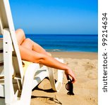 girl lying on a beach lounger with glasses in hand - stock photo