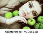 portrait of a beautiful girl with smoky eye makeup, lies in a bath with green apples - stock photo
