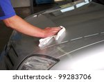 man is polishing the car hood - stock photo