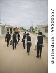 Small photo of Mariachi band walking and carrying their instruments