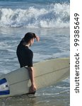 Young Man preparing to surf/Surfs Up!/ Man going out to the surf - stock photo