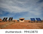 Full view of solar panels and building in desert - stock photo