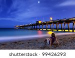woman sitting on Venice Beach, Florida at night, time exposure - stock photo