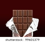chocolate bar with open cover on dark background - stock photo