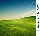 trace of airplane on the sky over green hills - stock photo