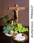 Holy communion image showing a golden chalice with grapes and bread wafers - stock photo