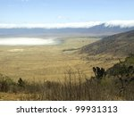 Ngorongoro crater with clouds hanging over the rim and lake Magadi in white. - stock photo