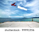 Flying banner pulled by airplane flying over a beautiful tropical beach - stock photo