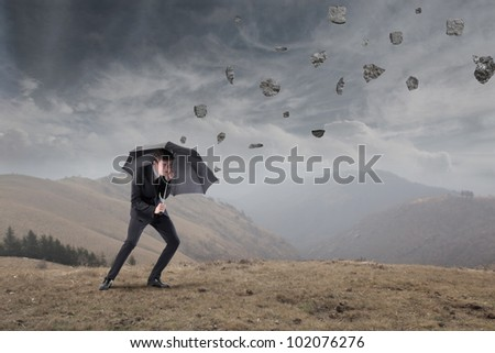businessman sheltering under an
