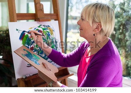 happy retired woman painting on