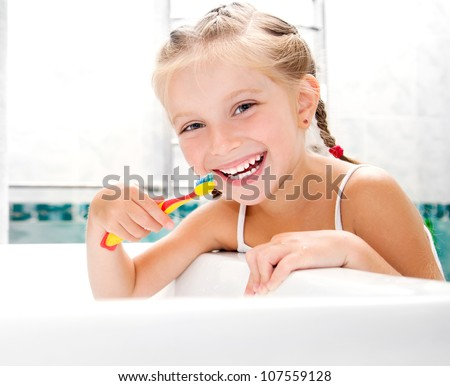 little girl brushing teeth in