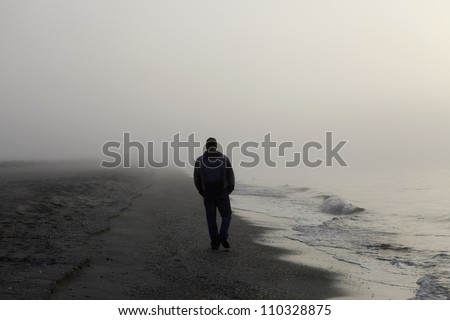lonely man walking on a foggy