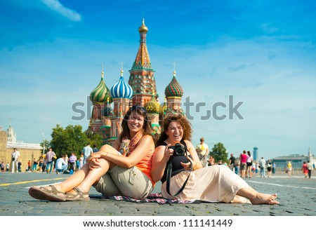 happy young women sitting on