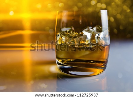 whisky with ice on a reflective