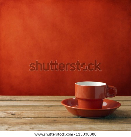 red coffee cup on wooden deck