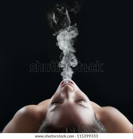 woman blowing smoke against