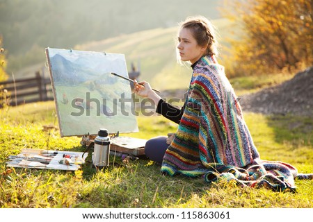 young artist painting an autumn