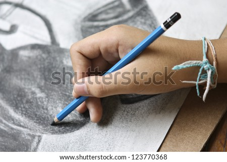 boy hands with pencil drawing