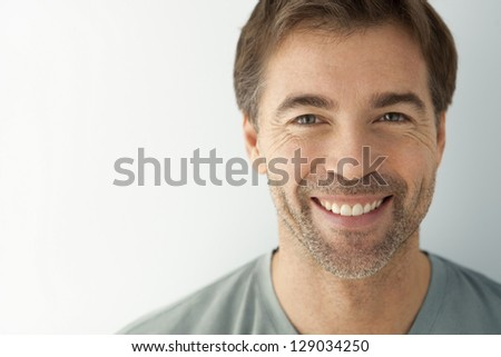 man with a toothy smile looking