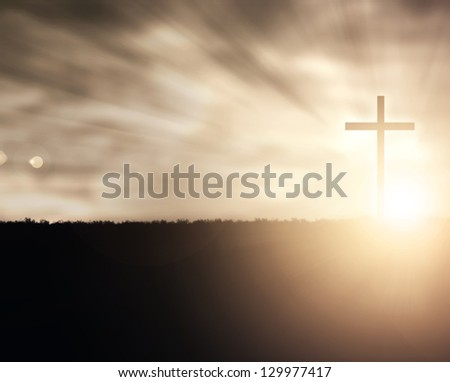 a christian cross at sunset